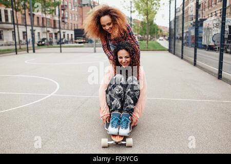 Femme poussant son ami sur la planche à roulettes. Les filles de patinage au basket-ball. Les jeunes femmes s'amuser Banque D'Images