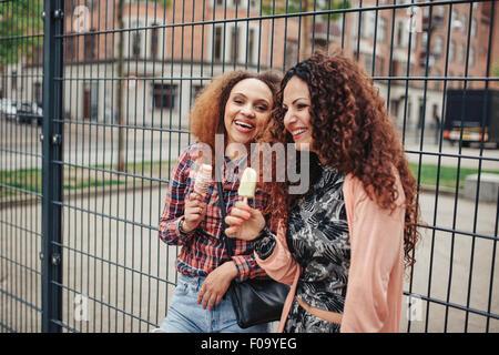 Heureux les femmes de manger une glace à l'extérieur. Girl friends having fun on city street. Banque D'Images