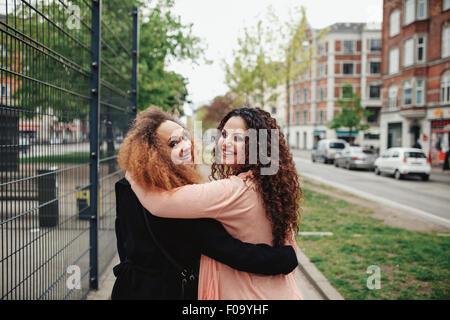 Tourné en plein air de deux copines marcher à travers la ville à la recherche de l'épaule plus souriant. Heureux Banque D'Images