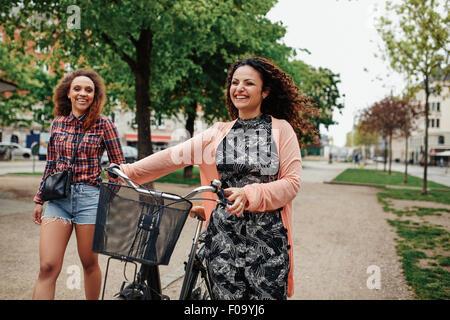 Souriante jeune amis marchant sur la rue de la ville, une femme pousse son vélo. Deux jeunes filles Hipster cycle Banque D'Images