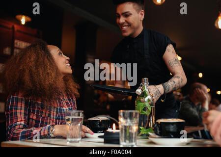 Femme parlant de serveur au restaurant. Jeune femme assise au café avec waiter standing en souriant. Banque D'Images