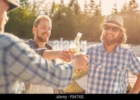 Les hommes de faire un toast avec les bouteilles de bière, smiling Banque D'Images