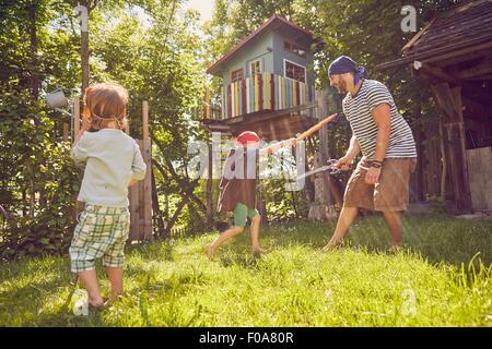 Son père et ses deux fils dans le jardin, portant les costumes, jouant avec la prétention swords Banque D'Images