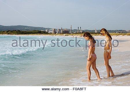 Deux jeunes amis féminins portant des bikinis paddling in sea Banque D'Images