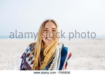 Portrait of young woman wrapped in blanket faisant sourire on beach Banque D'Images
