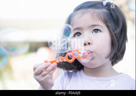 Young Girl blowing bubbles, close-up Banque D'Images