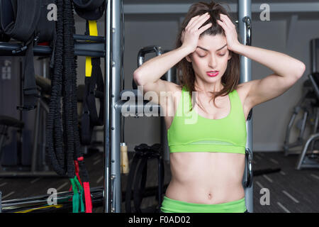 Portrait de jeune femme tenant sa tête dans les mains à la salle de sport Banque D'Images