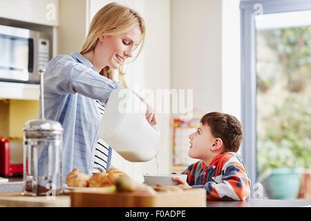 Verser le lait de la mère en fils bol petit déjeuner Banque D'Images