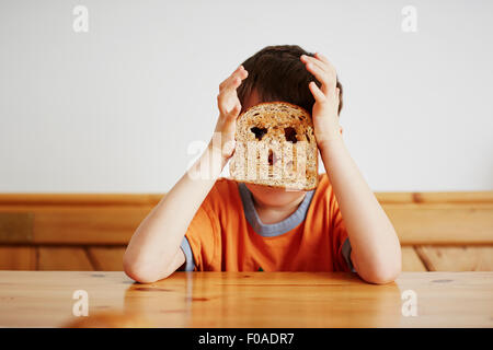 Jeune garçon couvrant le visage avec du pain grillé Banque D'Images