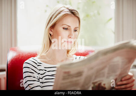 Mid adult woman reading newspaper Banque D'Images
