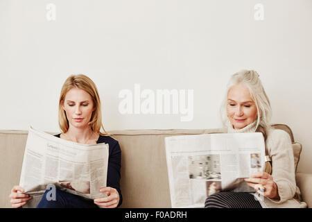 Cadres supérieurs et moyens des femmes adultes de lire les journaux Banque D'Images