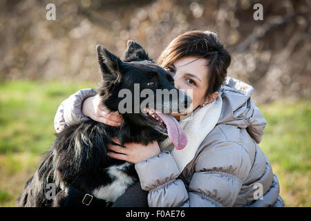 Portrait of mid adult woman kissing her dog in field Banque D'Images