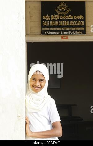 Jeune fille en uniforme debout à l'entrée de l'Association culturelle musulmane, Galle Fort, Sri Lanka Banque D'Images