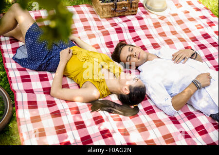 Jeune couple lying together on picnic blanket Banque D'Images