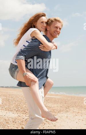 Man giving girlfriend piggyback un à la plage Banque D'Images