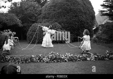 Un groupe de filles dansant dans un jardin Banque D'Images