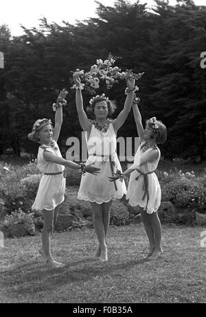 Deux adolescentes avec leur mère dansant dans un jardin portant des robes avec des colliers et bracelets de fleurs Banque D'Images