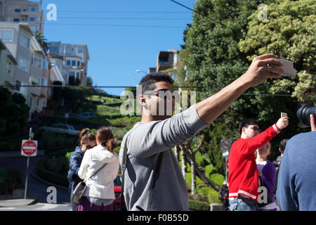 Un touriste pose pour une prise selfies avec son téléphone mobile en face de Lombard Street à San Francisco, Californie, Banque D'Images