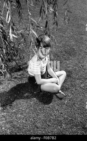 Un garçon assis sous un saule dans un jardin. Banque D'Images