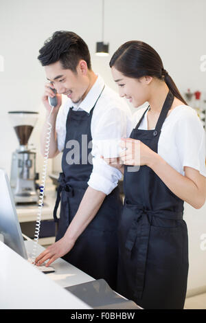Jeune couple working in coffee shop Banque D'Images
