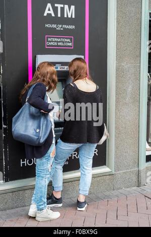 Deux femelles retirer de l'argent à un distributeur automatique à Bournemouth Dorset
