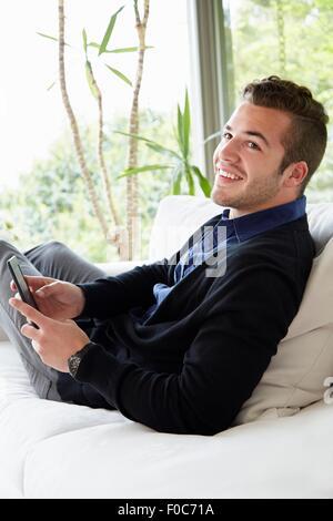 Portrait of man relaxing on sofa avec pieds en tenant l'appareil de lecture numérique Banque D'Images