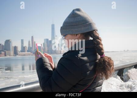 Young Girl taking photograph of skyline en utilisant smartphone, New York, NY, USA Banque D'Images