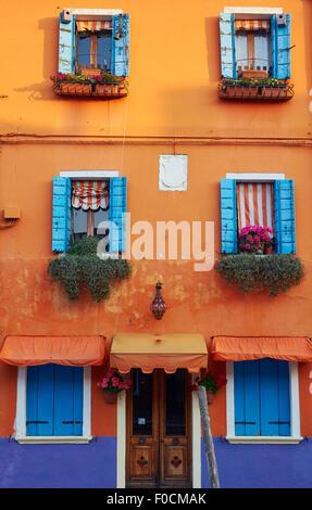 Orange maison aux volets bleus Burano Lagune de Venise Vénétie Italie Europe Banque D'Images