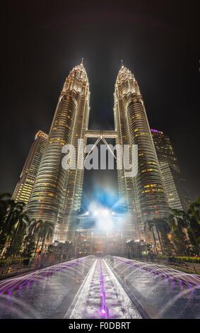 Fontaine en face de la tour Petronas illuminée la nuit, Kuala Lumpur, Malaisie Banque D'Images