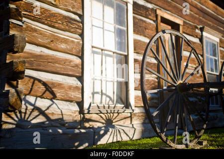 La lumière du soleil tôt le matin de jeter une ombre d'une grande roue de chariot en bois sur le côté d'une cabane Banque D'Images
