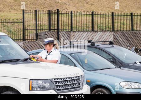 Un gardien de la circulation l'émission d'un ticket de parking sur front de Southend dans l'Essex. Banque D'Images