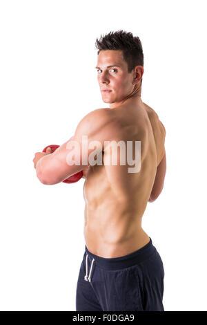 Beau Jeune homme tenant un disque de poids en studio shot, comme s'il lance ou jetant Banque D'Images
