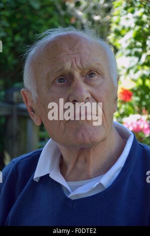 Un homme âgé souffrant de démence assis tranquillement à perdu dans ses propres pensées. Banque D'Images