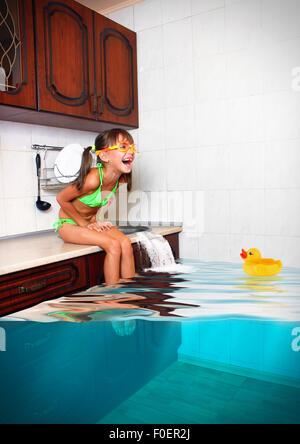 Fille enfant faire désordre, cuisine inondée imitant piscine, concept drôle Banque D'Images
