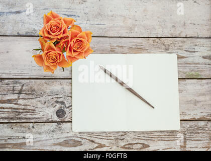 Trois roses orange sur table en bois rustique avec open notebook and pen Banque D'Images