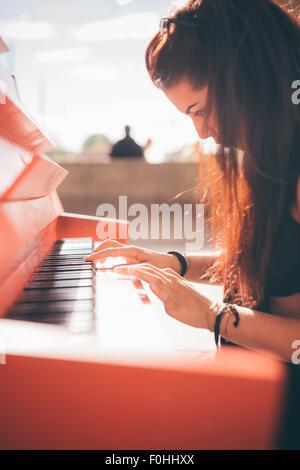 Close up d'un jeune beau cheveux brun rougeâtre caucasian girl playing piano - creative, performances, musique concept - elle est habillée avec une chemise noire et joue un piano rouge
