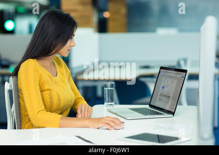 Young casual businesswoman using laptop in office Banque D'Images