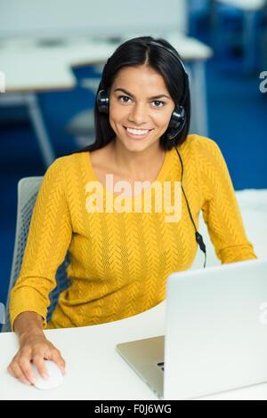 Smiling casual businesswoman in sweater assise à son lieu de travail avec les écouteurs en bureau et looking at Banque D'Images