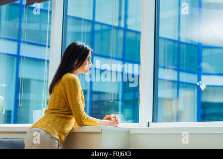 Portrait of a casual businesswoman looking at window in office
