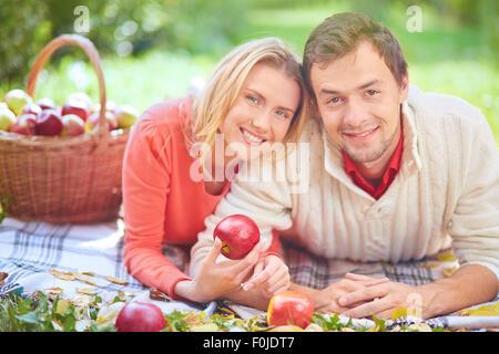 Beau couple avec pommes rouges passer du temps dans le parc Banque D'Images