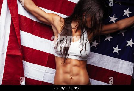 Athlète féminin holding drapeau américain à l'hôtel. Fit young woman wearing sports bar avec United States de drapeau Banque D'Images