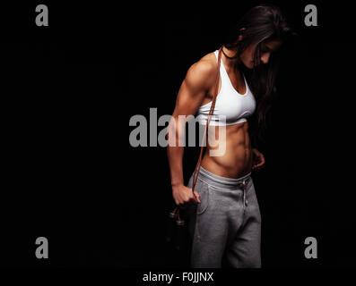 Portrait de jeune femme de remise en forme avec un saut à la corde. Bodybuilder féminin avec la corde à sauter à Banque D'Images