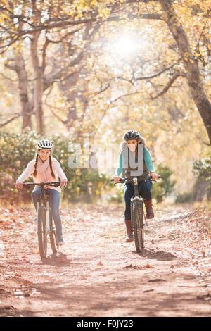 Mère et fille du vélo sur le chemin dans les bois Banque D'Images
