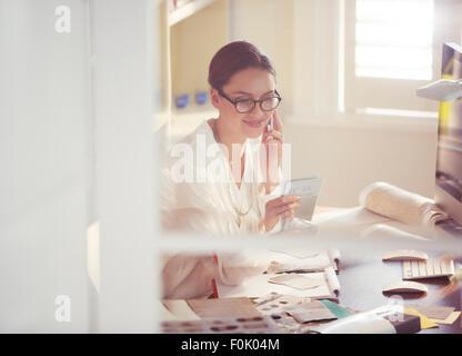 Architecte d'intérieur d'examiner et d'échantillons de tissus talking on cell phone in office Banque D'Images