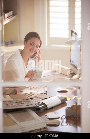 Architecte d'intérieur d'examiner et de nuances talking on cell phone in home office Banque D'Images