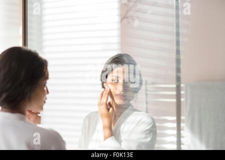 Woman applying moisturizer contre joue en miroir de salle de bains Banque D'Images