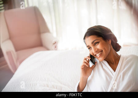 Smiling woman in bathrobe talking on cell phone on bed Banque D'Images