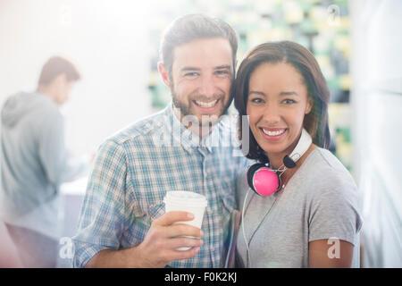 Smiling portrait des gens d'affaires créatifs avec des écouteurs et du café Banque D'Images