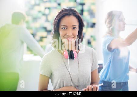 Creative businesswoman Portrait confiant avec des écouteurs in office Banque D'Images