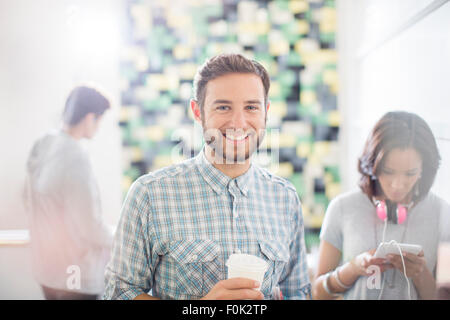 Portrait confiant creative businessman drinking coffee in office Banque D'Images